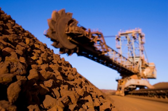 A stack reclaimer with a pile of iron ore at the Rio Tinto Parker Point ship loading terminal in Western Australia